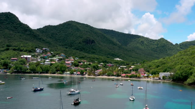 aerial flying over caribbean water towards the shore over anchored boats, daytime - french overseas territory stock videos & royalty-free footage