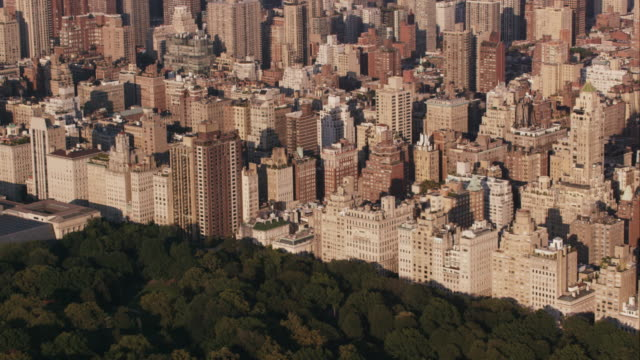aerial flying over central park heading north looking east a buildings along the park, nyc - museum stock videos & royalty-free footage