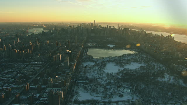 aerial flying over central park in manhattan looking south at new york city covered in snow nyc - central park manhattan video stock e b–roll