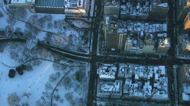 aerial flying over central park, metropolitan museum, and 5th avenue in manhattan looking directly down at park and streets covered in snow nyc - metropolitan museum of art new york city stock videos & royalty-free footage