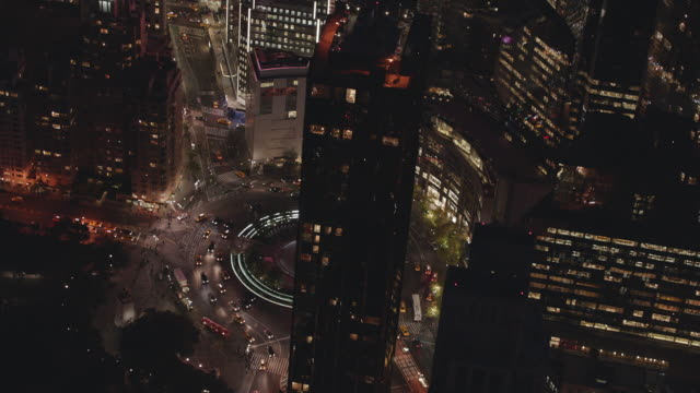 aerial flying over columbus circle as cars drive around at night with lights on in buildings and cars - columbus circle stock videos & royalty-free footage