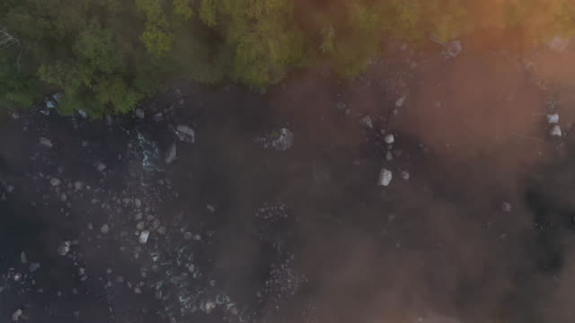 aerial flying over country landscape looking directly down on fog and river, at sunrise - ニューパルツ点の映像素材/bロール