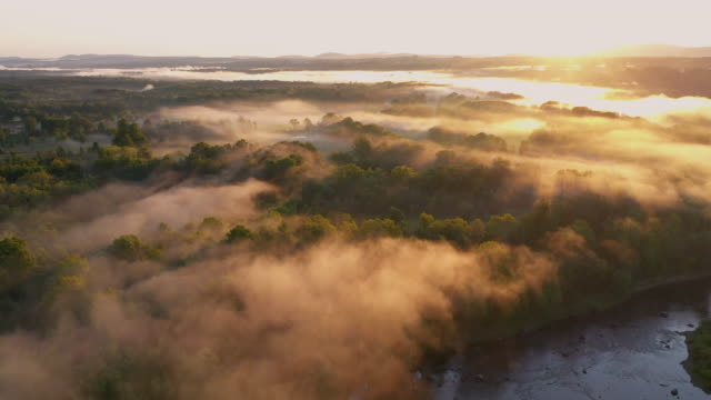 aerial flying over country landscape with fog over river, at sunrise - ニューパルツ点の映像素材/bロール