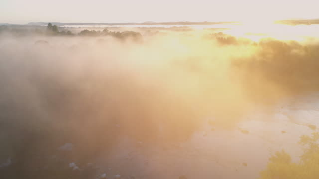 aerial flying over country landscape with fog over river, at sunrise - film tilt stock videos & royalty-free footage