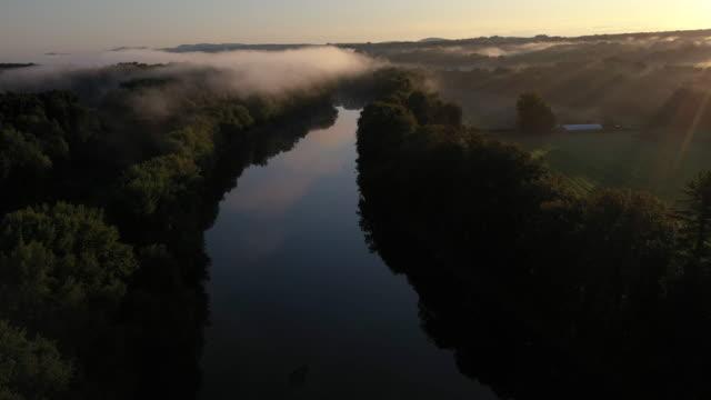 vidéos et rushes de aerial flying over country landscape with fog over river, at sunrise - comté d'ulster
