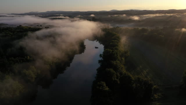aerial flying over country landscape with fog over river, at sunrise - beauty stock videos & royalty-free footage