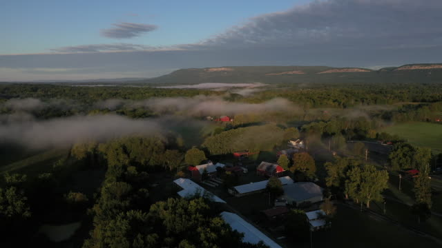 aerial flying over country landscape with fog over river, at sunrise - アルスター郡点の映像素材/bロール
