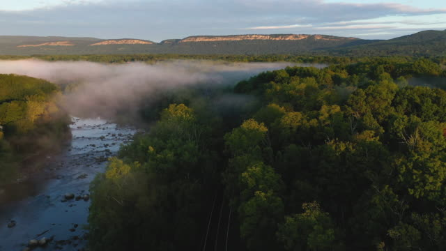 aerial flying over country landscape with low fog over river, at sunrise - ulster county stock videos & royalty-free footage