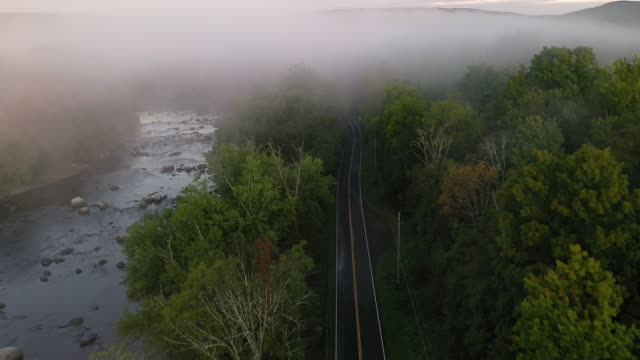 aerial flying over country road next to river with low fog over landscape, at sunrise - contea di ulster stato di new york video stock e b–roll
