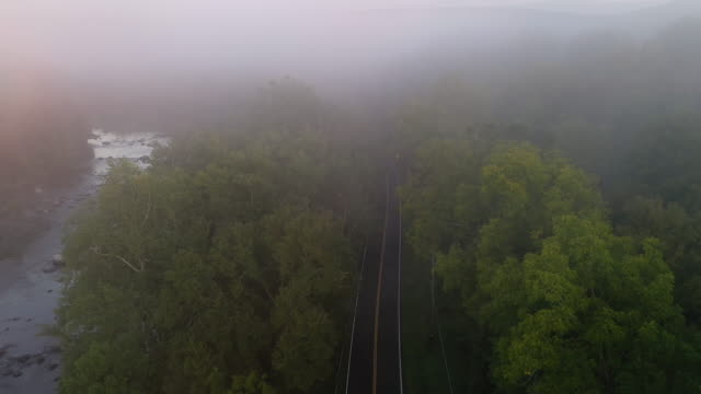 aerial flying over country road next to river with low fog over landscape, at sunrise - アルスター郡点の映像素材/bロール