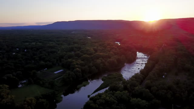 aerial flying over countryside at sunset - ニューパルツ点の映像素材/bロール