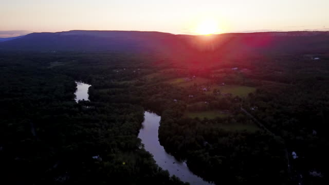 aerial flying over countryside with river at sunset - contea di ulster stato di new york video stock e b–roll