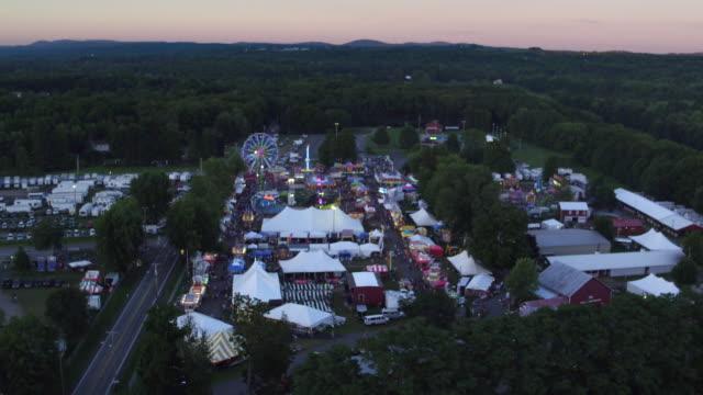 vídeos de stock, filmes e b-roll de aerial flying over county fair, sunset - new paltz