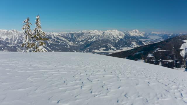 4k aerial flying over deep snow in winter mountains - schneebedeckt stock-videos und b-roll-filmmaterial