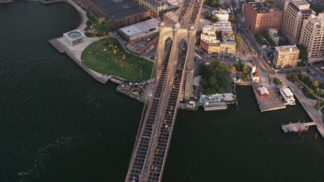vídeos de stock, filmes e b-roll de aerial flying over east river and brooklyn bridge into dumbo brooklyn, nyc - brooklyn new york