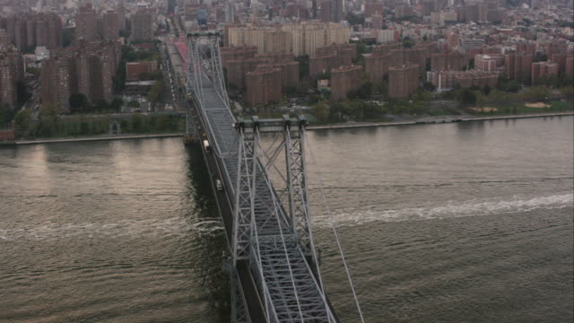vídeos de stock, filmes e b-roll de aerial flying over east river and williamsburg bridge following traffic into manhattan, nyc at sunset - williamsburg new york