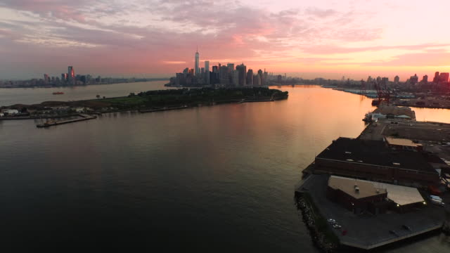Aerial flying over East River at sunrise view of lower Manhattan