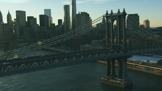 Aerial flying over East River looking at lower Manhattan snow covered, camera follows Manhattan bridge