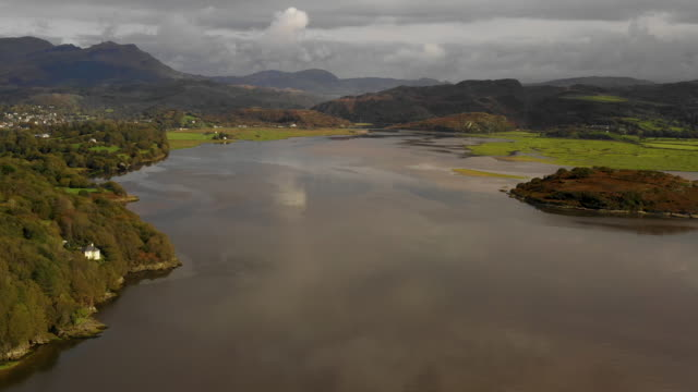 vidéos et rushes de aerial flying over estuary at high tide in north wales, daytime - pays de galles
