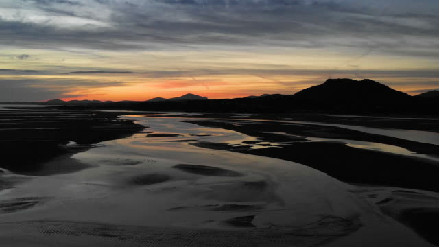 aerial flying over estuary at low tide in north wales, sunset - low tide stock videos & royalty-free footage