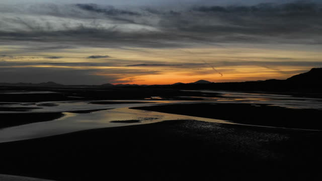 aerial flying over estuary at low tide in north wales, sunset - wales stock videos & royalty-free footage