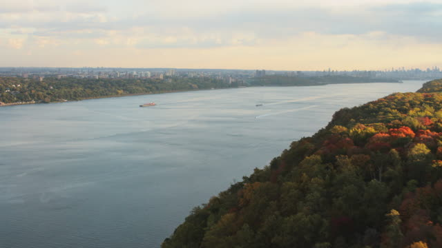 aerial flying over fall foliage and hudson river, nyc skyline in distance - hudson river stock videos & royalty-free footage