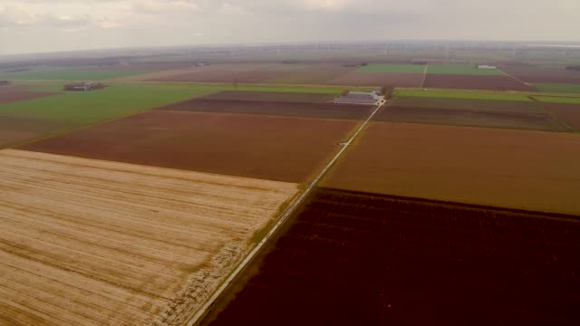 Aerial flying over farmland with windmills in the distance