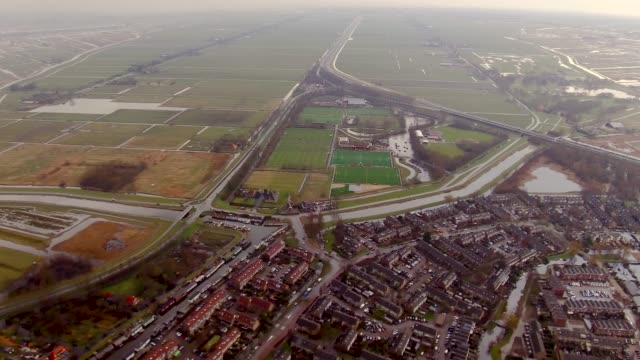 vidéos et rushes de aerial flying over field of land and water north of amsterdam, netherlands daytime - pays bas