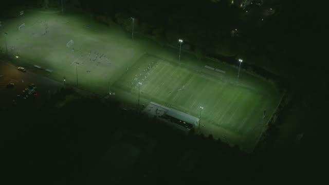 aerial flying over football field at night with lights on - アメリカンフットボール場点の映像素材/bロール