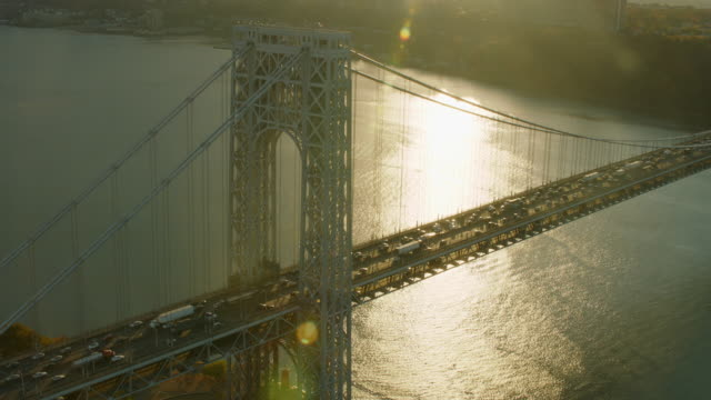 aerial flying over george washington bridge at sunset, lens flair - manhattan brücke stock-videos und b-roll-filmmaterial
