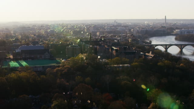vidéos et rushes de aerial flying over georgetown university in the morning with view of washington dc - georgetown washington dc