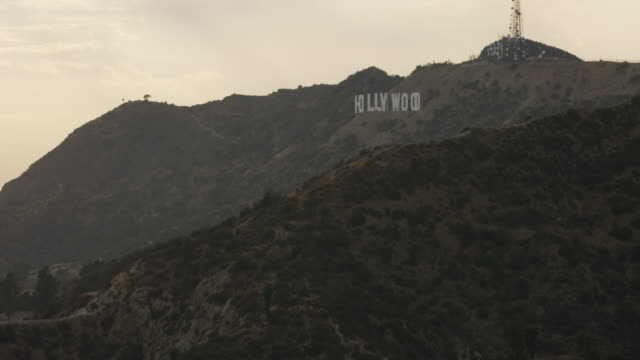 aerial flying over griffith park looking at hollywood sign la, ca late afternoon - hollywood sign stock videos & royalty-free footage