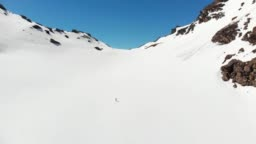 Aerial: flying over hiker walking towards snowy mountain top