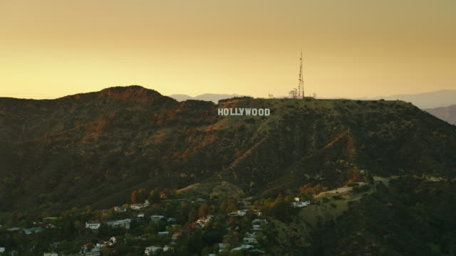 aerial pov flying over hollywood, ca, zoom into the hollywood sign, at sunset. - hollywood sign stock videos & royalty-free footage