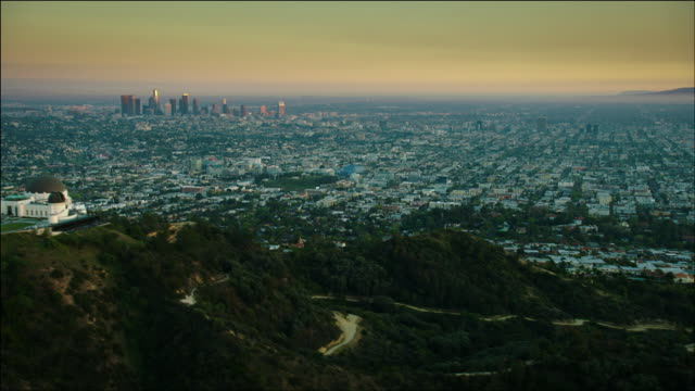 aerial pov flying over hollywood, moving past the griffith observatory, looking at downtown los angeles, ca, at sunset. - griffith observatory stock videos & royalty-free footage