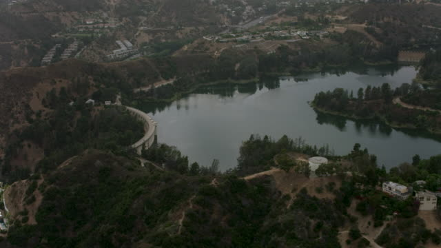 aerial flying over hollywood reservoir los angeles, ca sunset - reservoir stock videos and b-roll footage