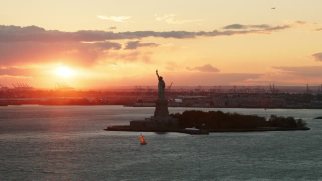 aerial flying over hudson river looking at statue of liberty with sailboat in front of it at sunset - sculpture stock videos and b-roll footage