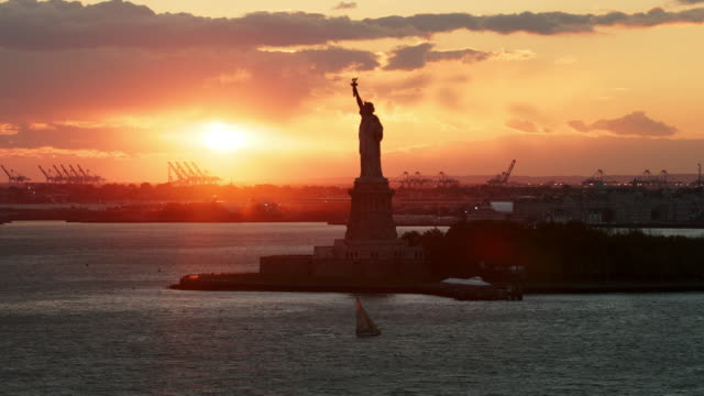 Aerial flying over Hudson River looking at Statue of Liberty with sailboat in front of it at sunset