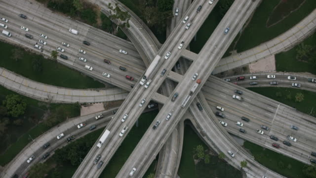 vídeos de stock, filmes e b-roll de aerial flying over interchange in los angeles, ca morning - entroncamento estrada