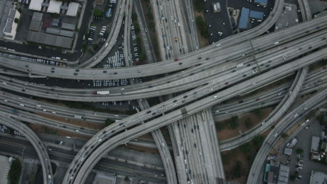 aerial flying over interchange in los angeles, ca morning - straßenüberführung stock-videos und b-roll-filmmaterial