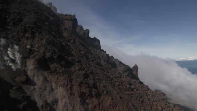 aerial flying over jagged flanksk, rock, clouds, augustine volcano, alaska, september 2011 - dom bildbanksvideor och videomaterial från bakom kulisserna