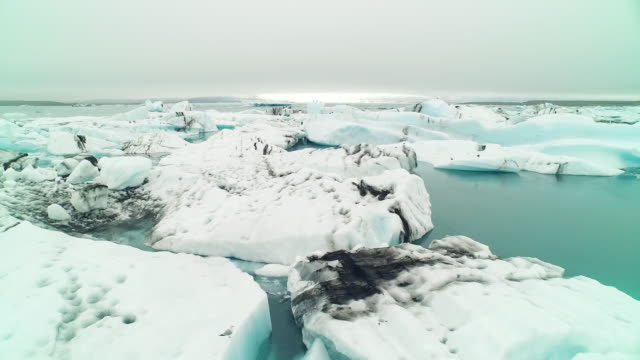 aerial flying over jã¶kulsã¡rlã³n glacier lagoon in iceland - jokulsarlon stock-videos und b-roll-filmmaterial