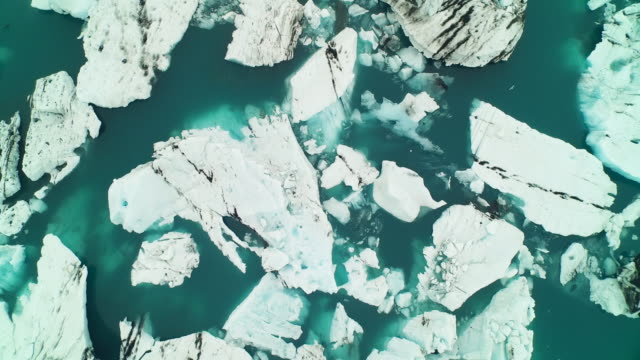 Aerial flying over Jökulsárlón glacier lagoon looking directly down zooming out in Iceland