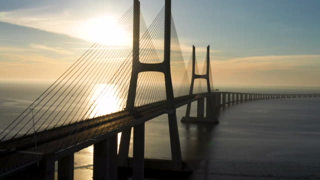 aerial flying over lisbon portugal looking at vasco da gama bridge, sunrise - ponte video stock e b–roll
