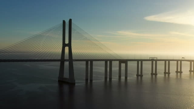 aerial flying over lisbon portugal looking at vasco da gama bridge, sunrise - portugal stock videos & royalty-free footage