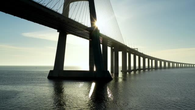 aerial flying over lisbon portugal looking at vasco da gama bridge, sunrise - cable stayed bridge stock videos & royalty-free footage