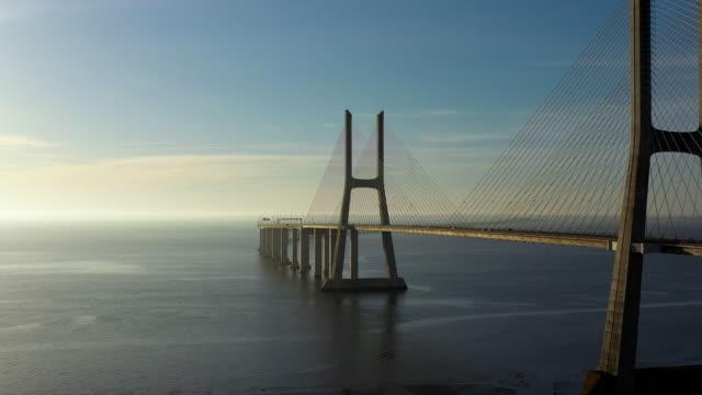 vídeos de stock e filmes b-roll de aerial flying over lisbon portugal looking at vasco da gama bridge, sunrise - portugal