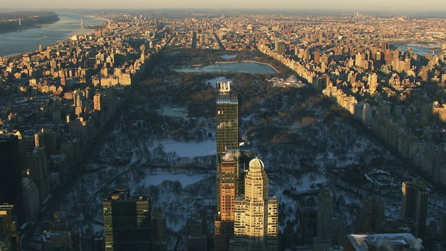 Aerial flying over midtown Manhattan looking north at Central Park covered in snow NYC