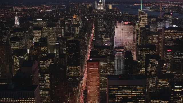 Aerial flying over midtown Manhattan looking south at night with lights on in buildings and cars, Empire State building and World Traid center in distance