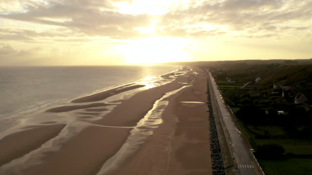 vidéos et rushes de aerial flying over omaha beach in france at sunrise - cliff